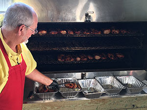 Hal Bennett pulling ribs out of rotissery for one of Johnston's Great Souther BBQ Fundraisers